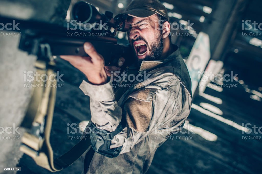 Soldier is creaming. He is looking through lens because he is taking aim. Guy is redady to shoot from the rifle stock photo