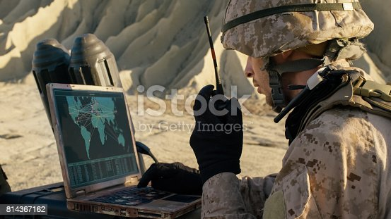 istock Soldier is Using Laptop Computer and Radio for Communication During Military Operation in the Desert. 814367162