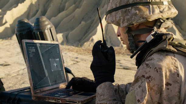 soldier is using laptop computer for tracking the target and radio for communication during military operation in the desert - armed forces stock photos and pictures