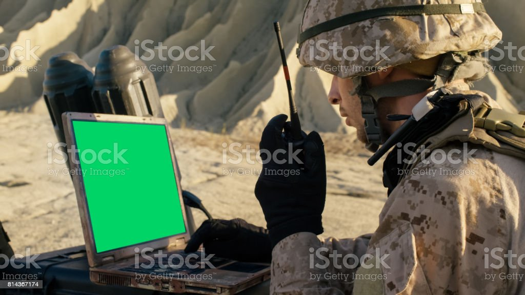 Soldier is Using Laptop Computer with Green Screen and Radio for Communication During Military Operation in the Desert. stock photo