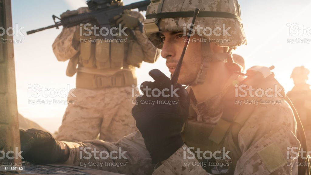 Soldier is Using Radio For Communication During Military Operation in the Desert stock photo
