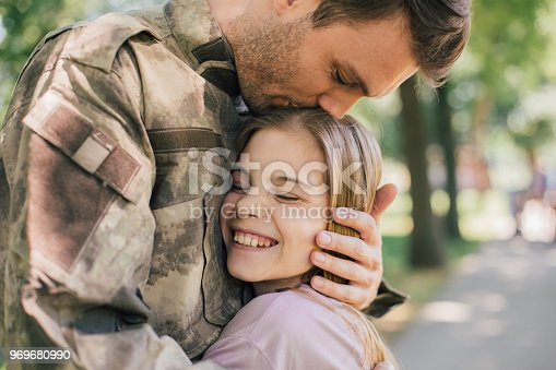 Young military officer hugging and kissing his daughter