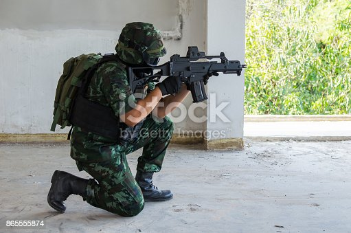 istock Soldier knee down hold the gun toward front 865555874