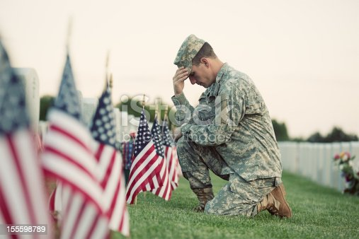 A soldier in ACU fatigues kneels in front of a grave with several American flags in front of it.  There is bright green grass under all, and another row of markers is behind the soldier, with flowers in front of them.
