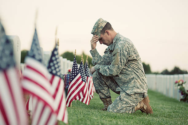 soldier kneeling at grave - memorial day stock pictures, royalty-free photos & images
