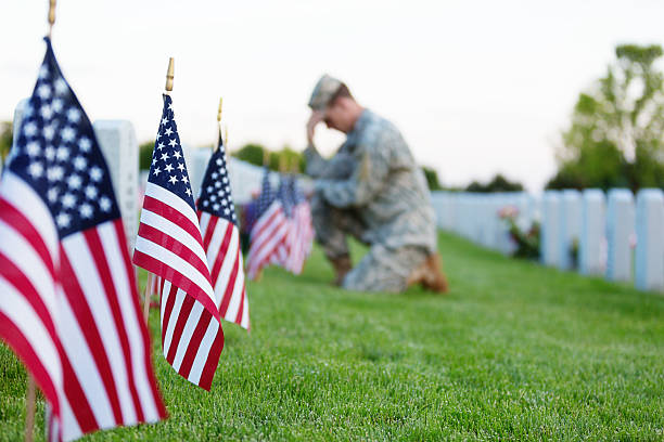 soldier kneeling at grave - war memorial stock pictures, royalty-free photos & images