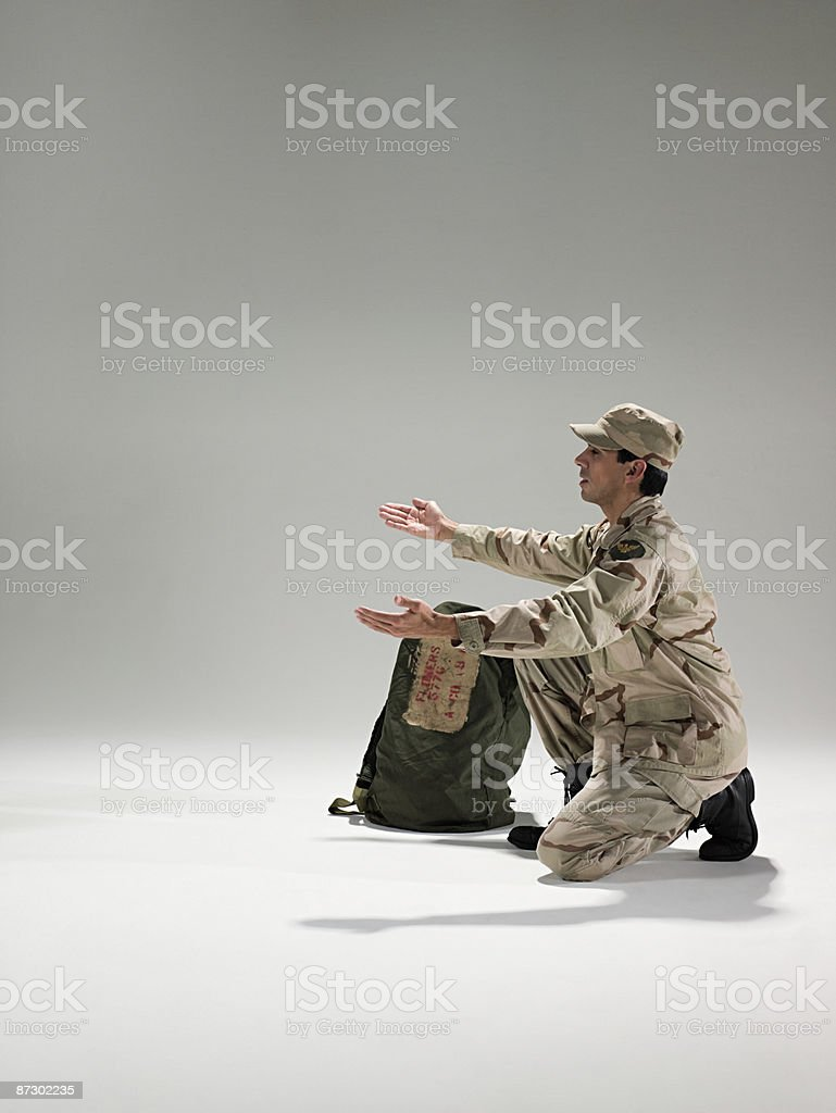 Soldier kneeling with open arms royalty-free stock photo