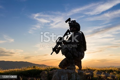 Soldier knelt in the field looking ahead