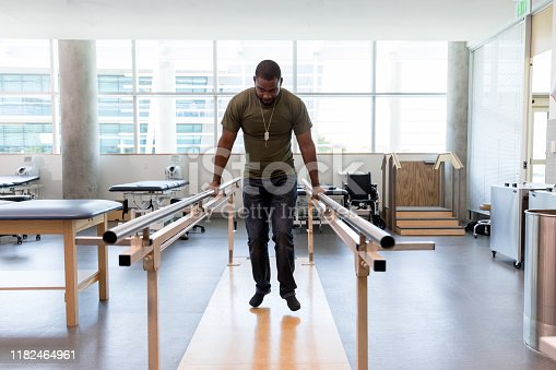 Mid adult military soldier uses parallel bars in a rehab center.