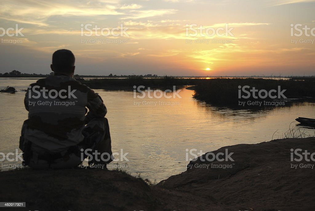 Soldier look sunset and think in Africa stock photo