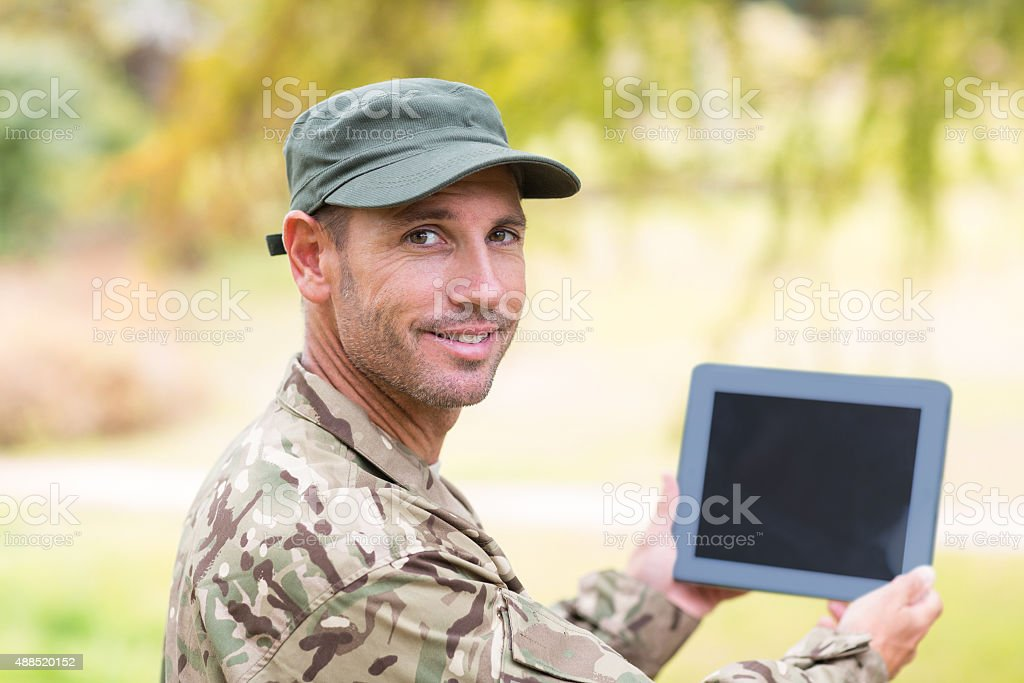Soldier looking at tablet pc in park stock photo