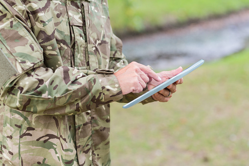 Soldier Looking At Tablet Pc In Park Stock Photo - Download Image Now