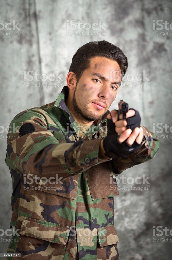 soldier militar latin man pointing a gun stock photo