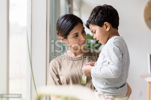 As she stands by the window of their home carrying her young son, the mid adult single mother listens quietly as the boy talks about her deployment.