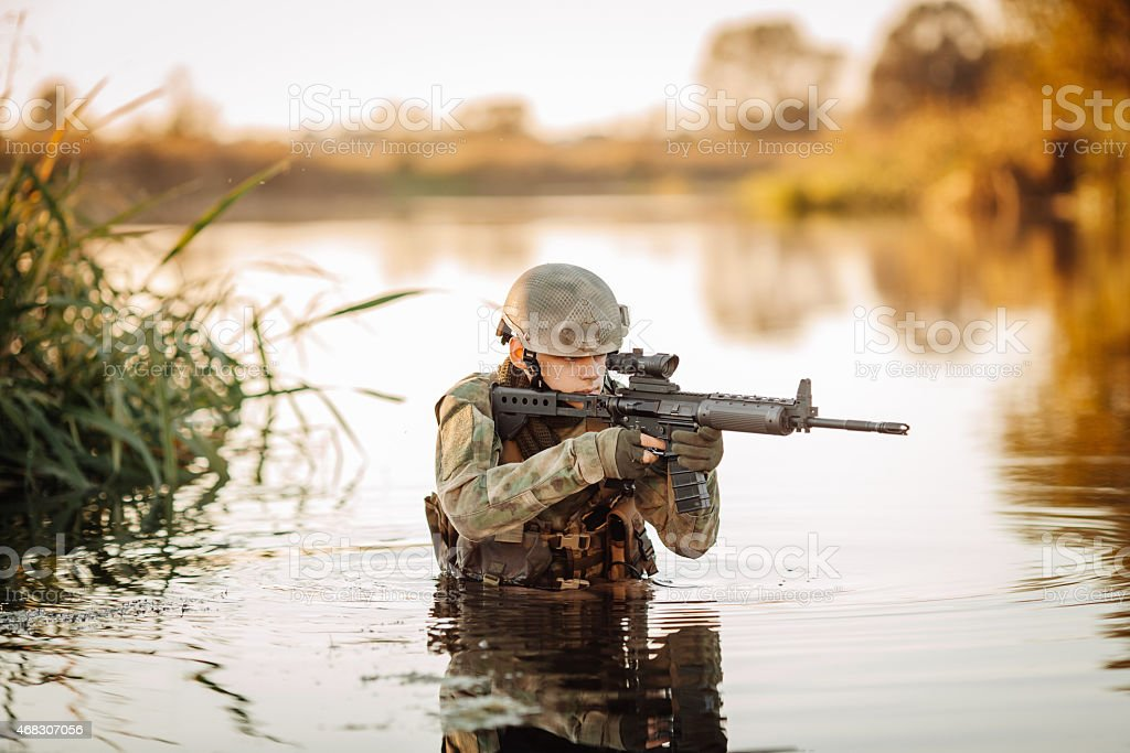 Soldier moving through the water and aiming at the enemy stock photo