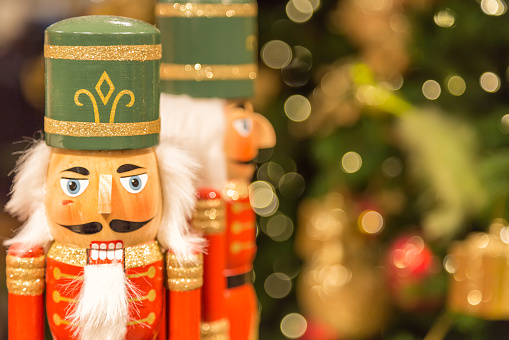 Soldier nutcracker statues standing in front of decorated Christmas tree with bokeh lights