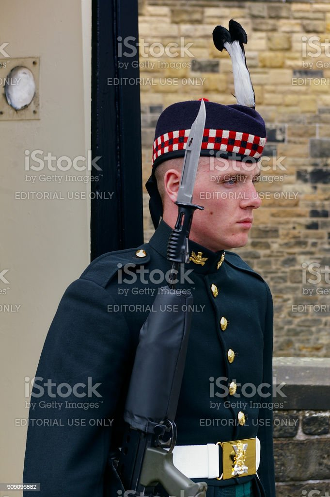 Soldier of the Royal Regiment of Scotland in full dress uniform carrying his rifle with fixed bayonet guarding the entrance of Edinburgh Castle stock photo