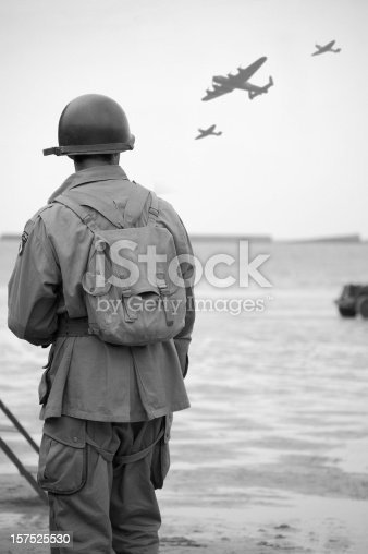 WW2 US Soldier looks towards the sky to see fly-past of Two spitfire planes and a Lancaster Bomber.Taken at the 65TH Anniversary of D-Day Normandy.Picture has been aged to give the feel of a vintage  photograph reenactment.
