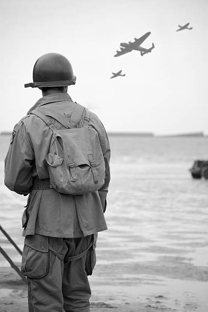 Soldier on  Omaha Beach. WW2 US Soldier looks towards the sky to see fly-past of Two spitfire planes and a Lancaster Bomber.Taken at the 65TH Anniversary of D-Day Normandy.Picture has been aged to give the feel of a vintage  photograph reenactment.  bomber plane stock pictures, royalty-free photos & images