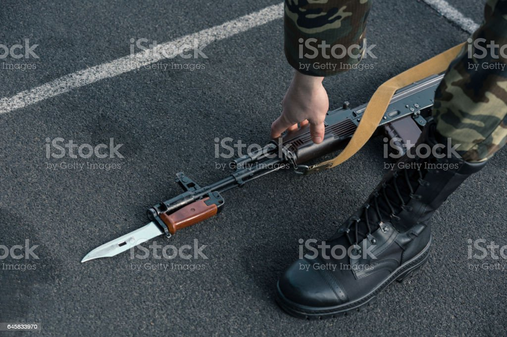Soldier picking his Assault rifle with Bayonet up from ground stock photo