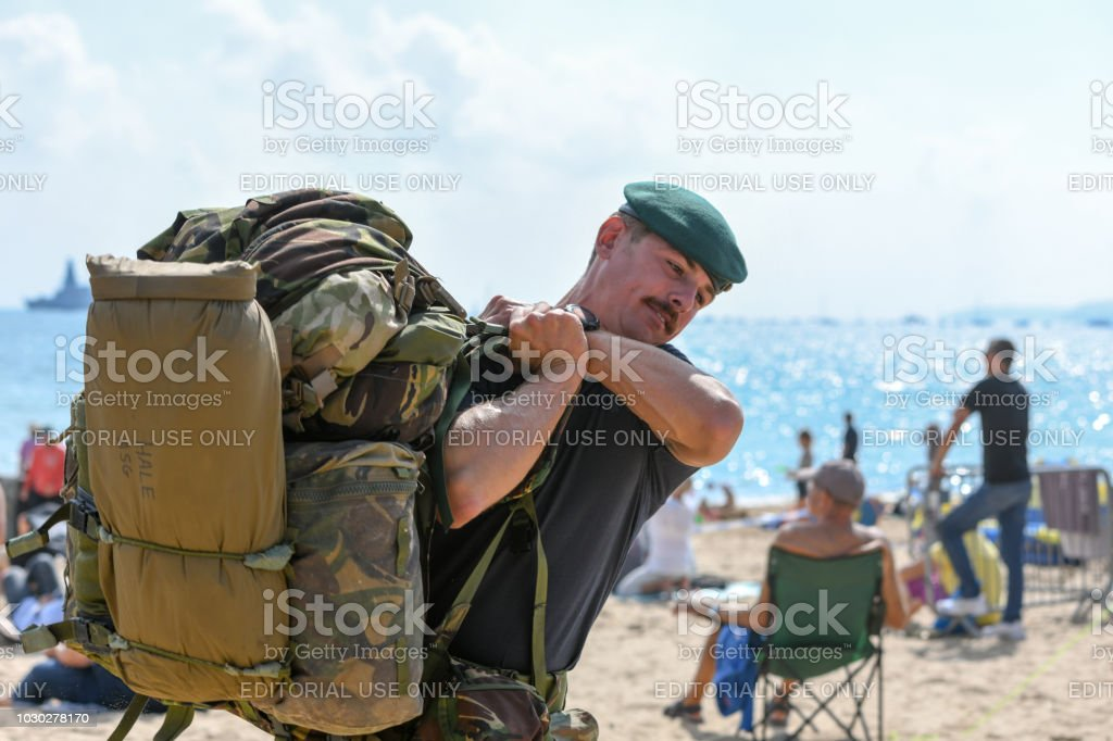 Soldier picks up a large kit bag, ruck sack, on the beach stock photo