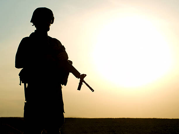 US soldier Silhouette of US soldier with rifle against a sunset Afghanistan stock pictures, royalty-free photos & images