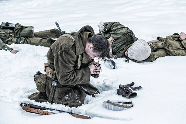 WWII Soldier Praying For Ambushed Comrade War Casualties A single survivor WWII US Army soldier kneeling in the snow mourning and praying with rosary beads on a frozen winter battlefield surrounded by dead friends and comrades - ambushed combat infantry war casualties. ambush stock pictures, royalty-free photos & images
