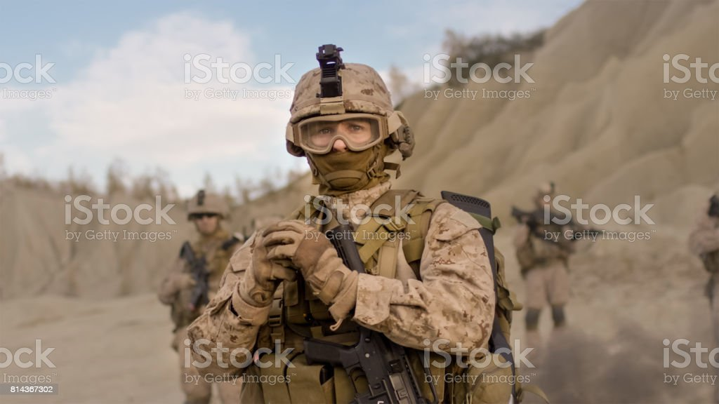 Soldier Preparing a Grenade for Throwing during Combat in the Desert. stock photo