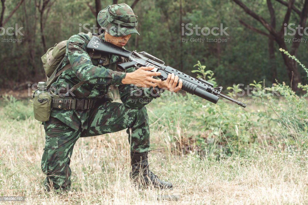 Soldier reloading his assault rifle. Chinese professional soldier reloading his weapon and putting his magzine inside his gun. Kneeing down action. - Royalty-free Adult Stock Photo