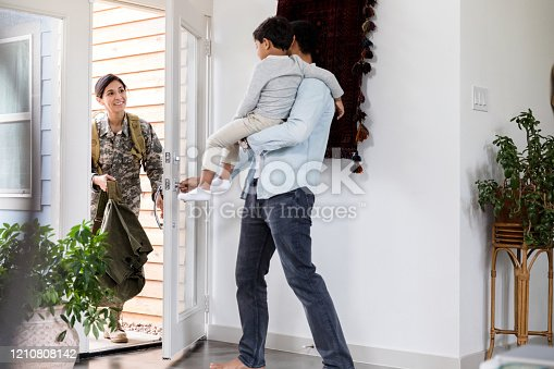 Excited female soldier returns home from a long deployment. She is greeted by her husband and preschool age son.
