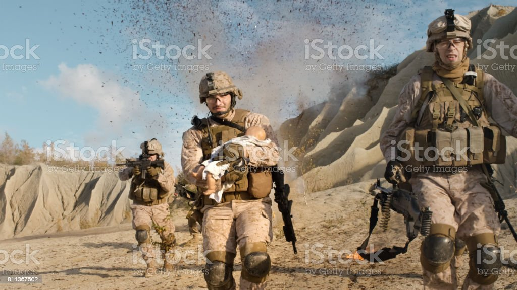 Soldier Running away from Explosions behind Carrying a Baby. While other Members of the Squad Covering Them During Battle in the Desert. stock photo