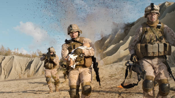 Soldier Running away from Explosions behind Carrying a Baby. While other Members of the Squad Covering Them During Battle in the Desert. Soldier Running away from Explosions behind Carrying a Baby. While other Members of the Squad Covering Them During Battle in the Desert. Afghanistan stock pictures, royalty-free photos & images