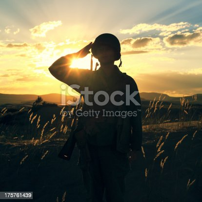 A World War 2 army soldier saluting with sunset behind him. Authentic WW2 army uniform.