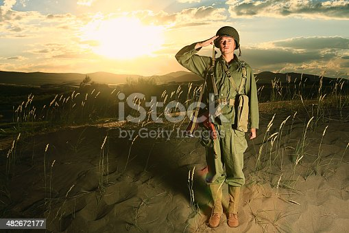 A World War 2 army soldier saluting with sunset behind him. Authentic WW2 army uniform. More vintage military photos.