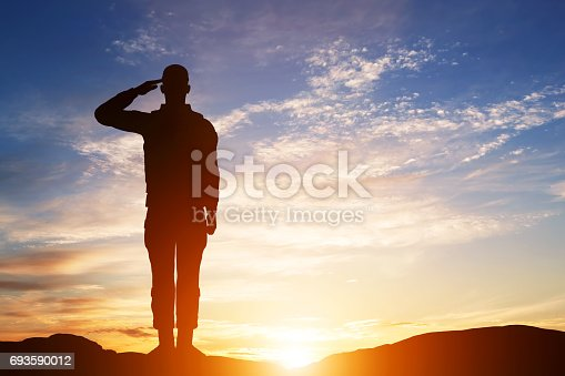 istock Soldier salute. Silhouette on sunset sky. Army, military. 693590012