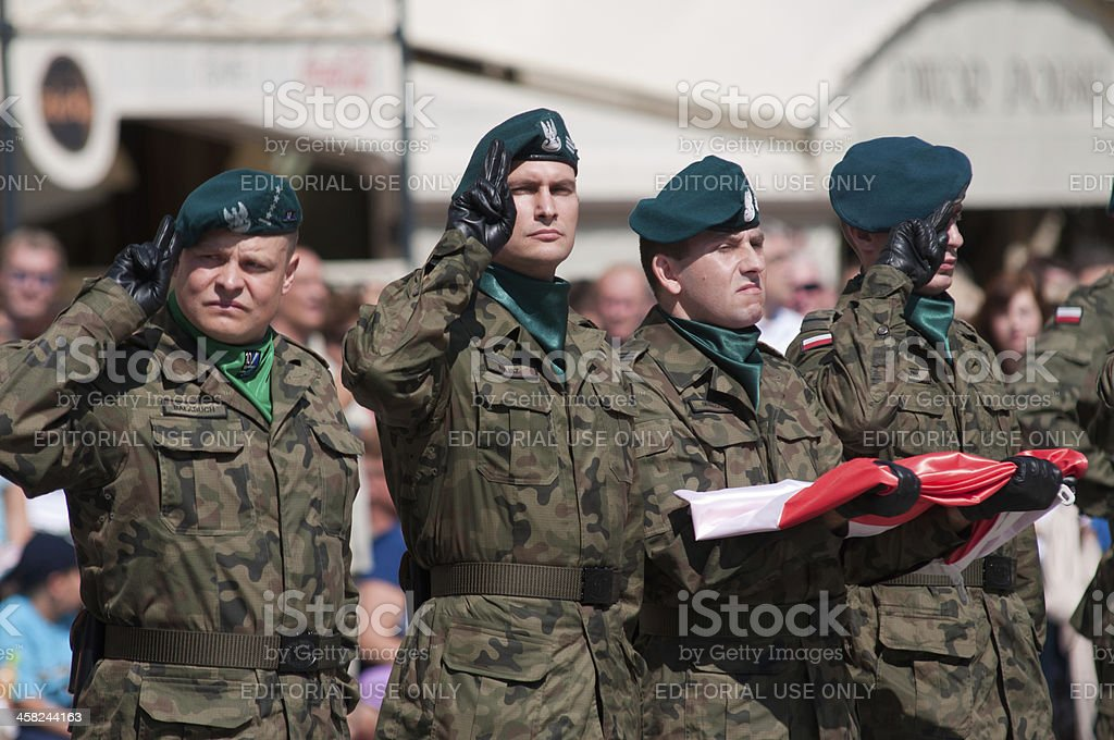 Soldier salute with Polish flag in hand royalty-free stock photo