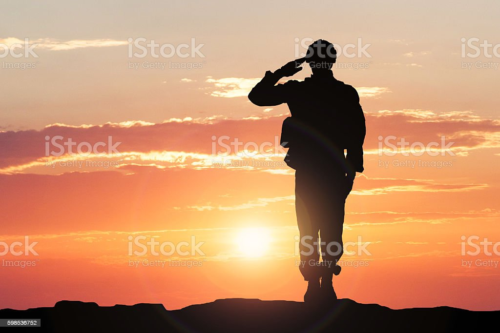 Soldier Saluting During Sunset stock photo