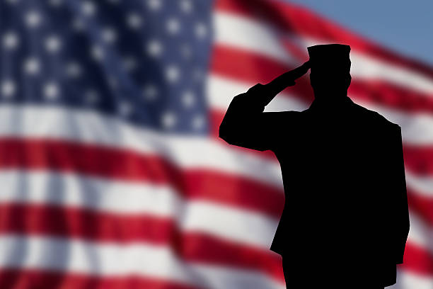 soldier saluting the usa flag for memorial day - saluting stock photos and pictures
