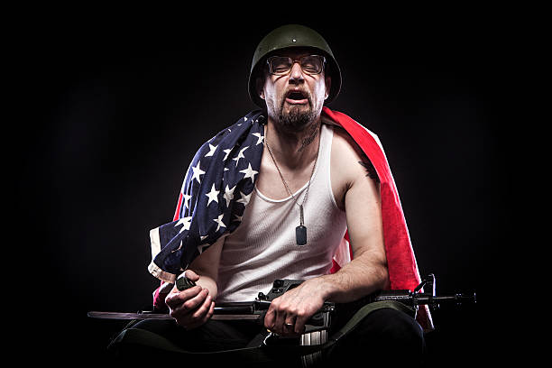 """Soldier Sitting, American Flag Across Shoulders, Crying with Mouth Open """"An American soldier sits against a black background with an American flag draped across his shoulders. His eyes are closed and his mouth is open in an expression of turmoil. He is wearing a navy-green combat helmet, a white tank top, dog tags, and black pants. He holds a grenade in one hand and a rifle across his lap."""" american flag tattoos for men stock pictures, royalty-free photos & images"""