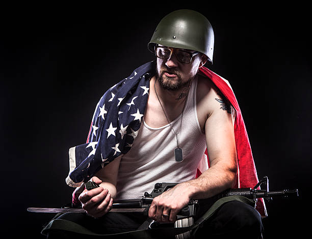 """Soldier Sitting, American Flag Across Shoulders, Grenade in Hand """"An American soldier sits pensively against a black background wearing an American flag across his shoulders. He is also wearing a navy-green combat helmet, glasses, a white tank top, dog tags, and black pants. He holds a grenade in one hand and a rifle across his lap. His eyes are closed."""" american flag tattoos for men stock pictures, royalty-free photos & images"""
