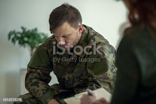 istock Soldier sitting and talking to his therapist 1014213076