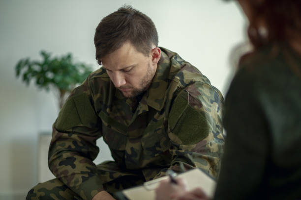 Soldier sitting and talking to his therapist Soldier sitting and talking to his therapist post traumatic stress disorder stock pictures, royalty-free photos & images