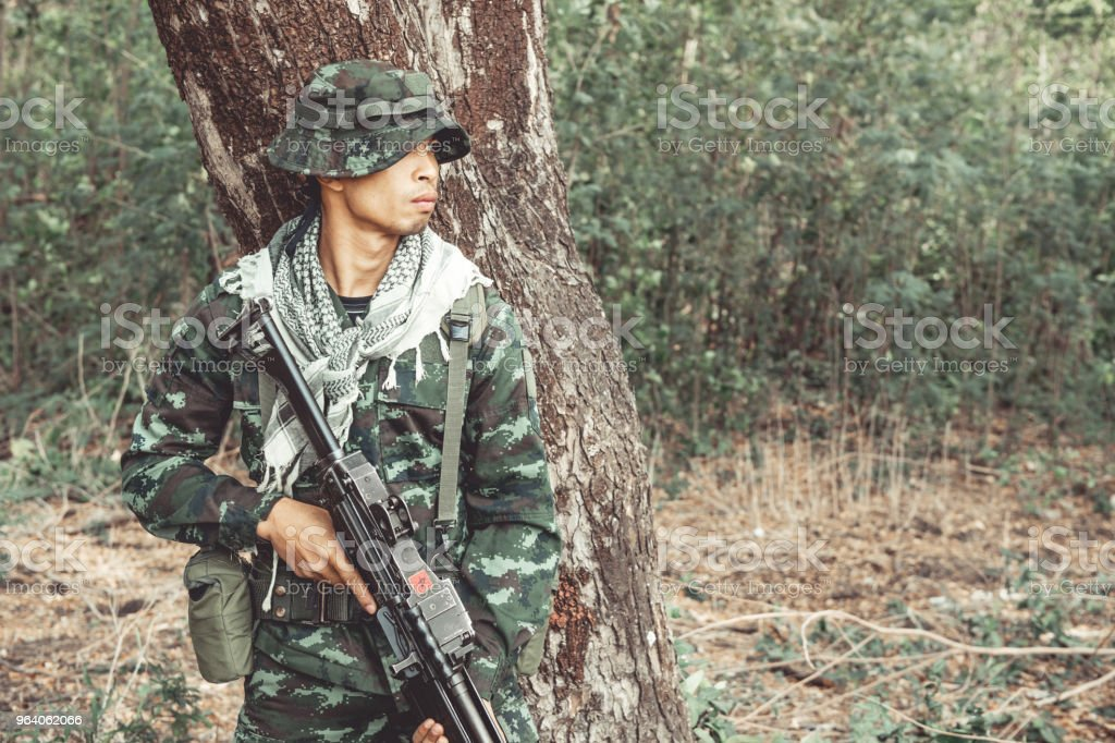 Soldier standing behind a tree ready to attack. Chinese male soldier standing behind a large tree looking around for his ememy. - Royalty-free Adult Stock Photo