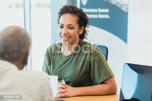 Soldier waits with hands clasped as finance professional reviews paperwork