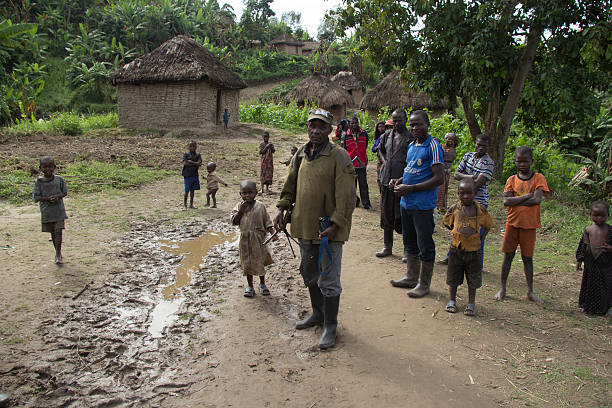 FDLR Soldier walking with Rwandan Refugees Chai, North Kivu, DRC- March 29, 2014: FDLR soldier walking with Rwandan refugees in Chai, North Kivu, DR Congo. genocide stock pictures, royalty-free photos & images