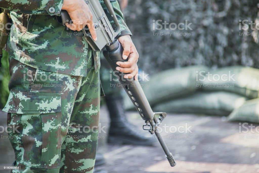 soldier with Colt M16 gun stand guard to security military camp stock photo