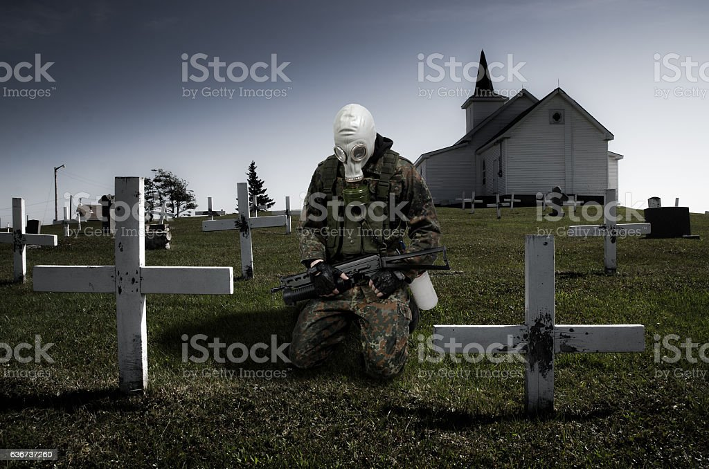 Soldier with gas mask kneeling in cemetery stock photo