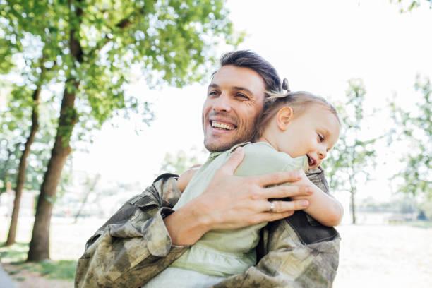 soldat mit seiner tochter - camouflagekleidung mädchen stock-fotos und bilder
