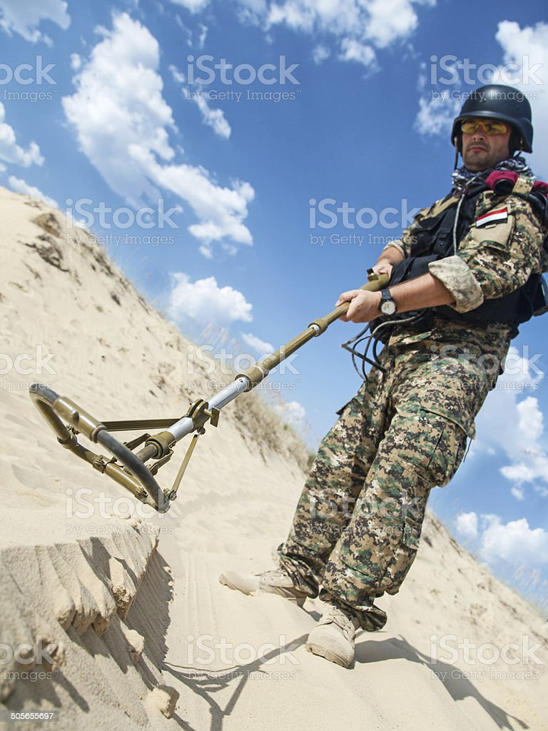 soldier with metal detector stock photo