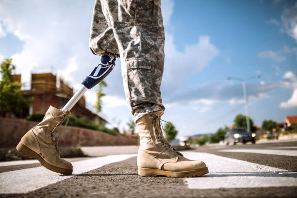 Soldier with prosthetic leg crossing road Unrecognizable soldier with artificial leg walking on pedestrian crossing on day, low angle view military lifestyle stock pictures, royalty-free photos & images